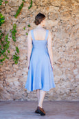 Picture from the back: woman walking in baby blue linen dress with straps and wide skirt