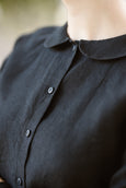 Woman wearing black minimalist linen shirt with long sleeves, up close image of a collar