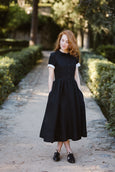 Woman wearing black classic dress with short sleeves, image from the front