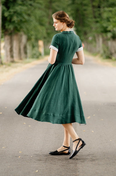 Woman wearing denim minimalist linen shirt with long sleeves, image from the side