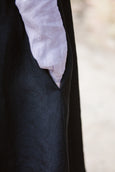 Woman wearing black linen flattering apron, up close image of a pocket