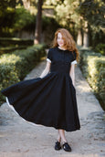 Woman wearing black classic dress with short sleeves, picture from the front