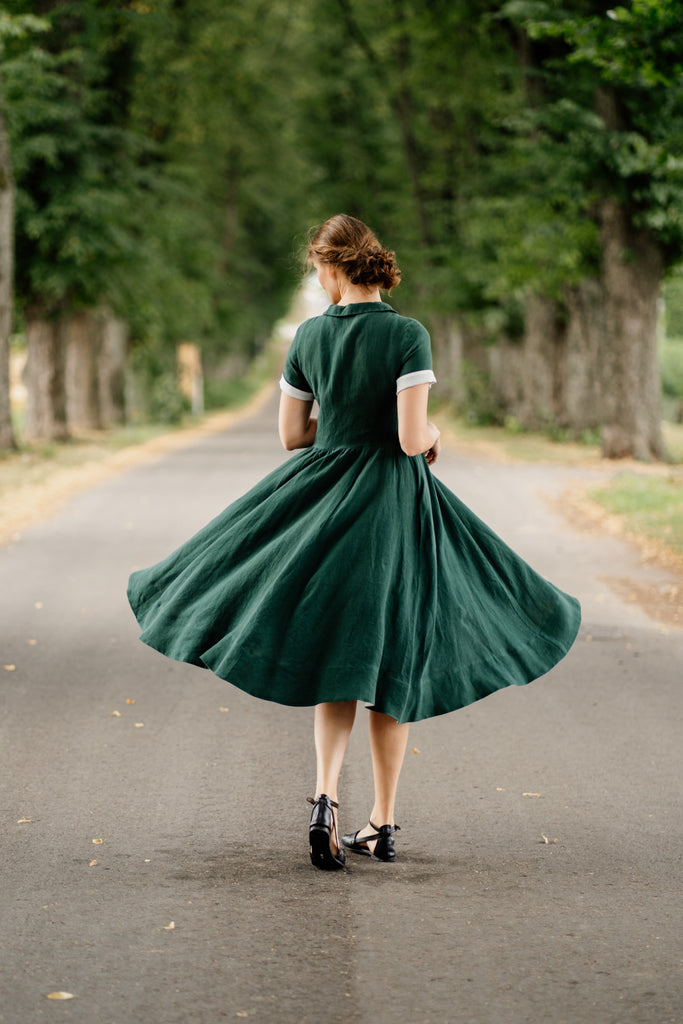 Woman in evergreen elegant linen dress, pictured from the back
