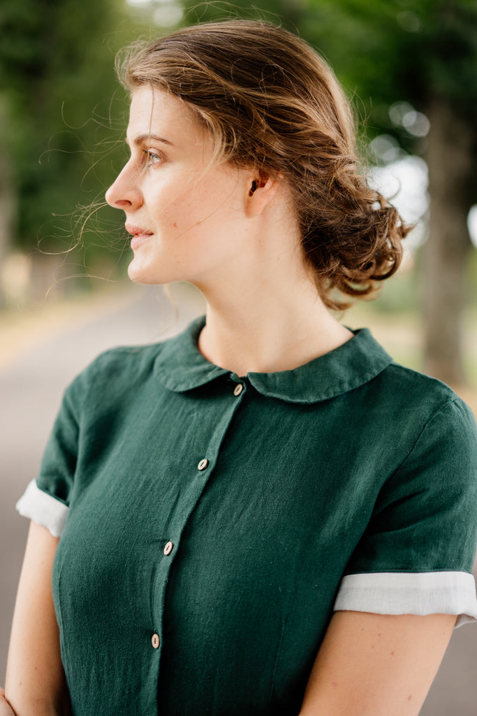 Woman in linen dress with Peter Pan collar, up close image from the front