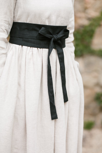 Woman wearing black ribbon belt, up-close picture from the side.