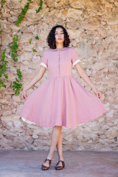 Woman in a short pastel pink linen dress with short sleeves