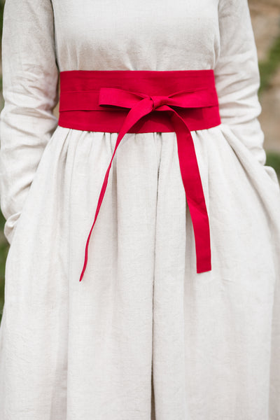 Woman wearing red ribbon belt, up-close image from the front.