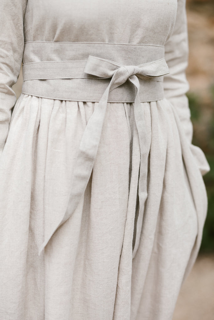 Woman wearing natural linen ribbon belt, up-close picture from the front.