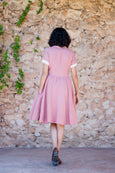 A photo from the back: woman walking in light pink linen dress with short sleeves
