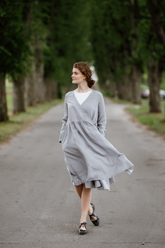 Model wearing grey color wrap dress with long sleeves, picture from the front