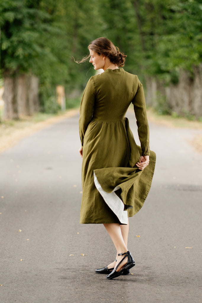 Woman wearing grey color minimalist linen shirt with long sleeves, up close image from the front