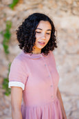 Up close picture of woman wearing rose pink linen dress with white rolled up sleeves