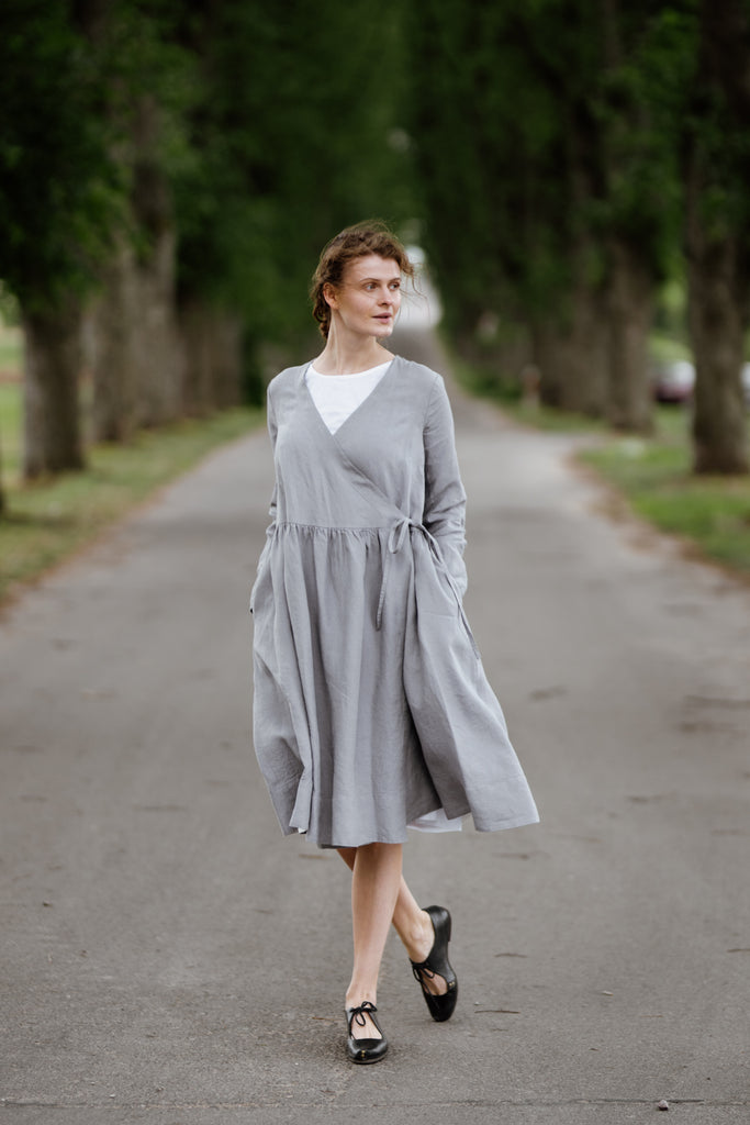 Woman wearing grey color wrap dress with long sleeves, image from the front