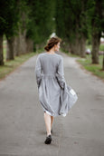 Woman wearing grey color wrap dress with long sleeves, picture from the back