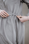 Woman wearing grey color wrap dress with long sleeves, up close image from the side