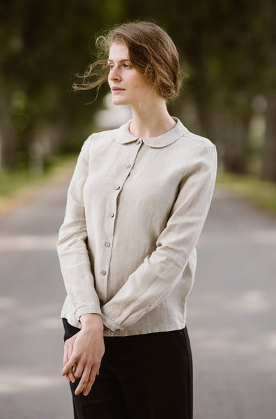 Woman wearing natural linen minimalist shirt with long sleeves, image from the front