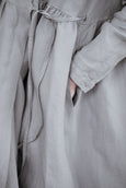Woman wearing grey color wrap dress with long sleeves, up close image of a pocket