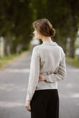 Woman wearing natural linen minimalist shirt with long sleeves, image from the back