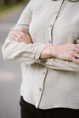 Woman wearing natural linen minimalist shirt with long sleeves, up close image from the front