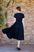 Photo from the back: woman wearing black linen dress with wide a-line skirt