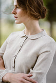 Woman wearing natural linen minimalist shirt with long sleeves, up close image from the side