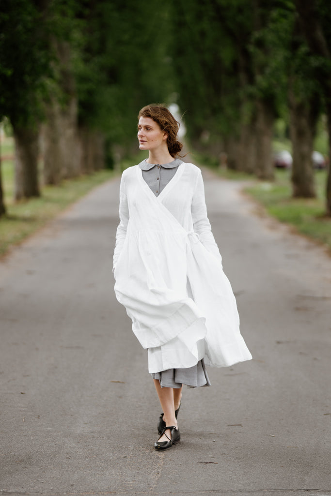 Model wearing white wrap dress with long sleeves, image from the front