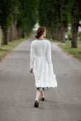 Woman wearing white wrap dress with long sleeves, picture from the back