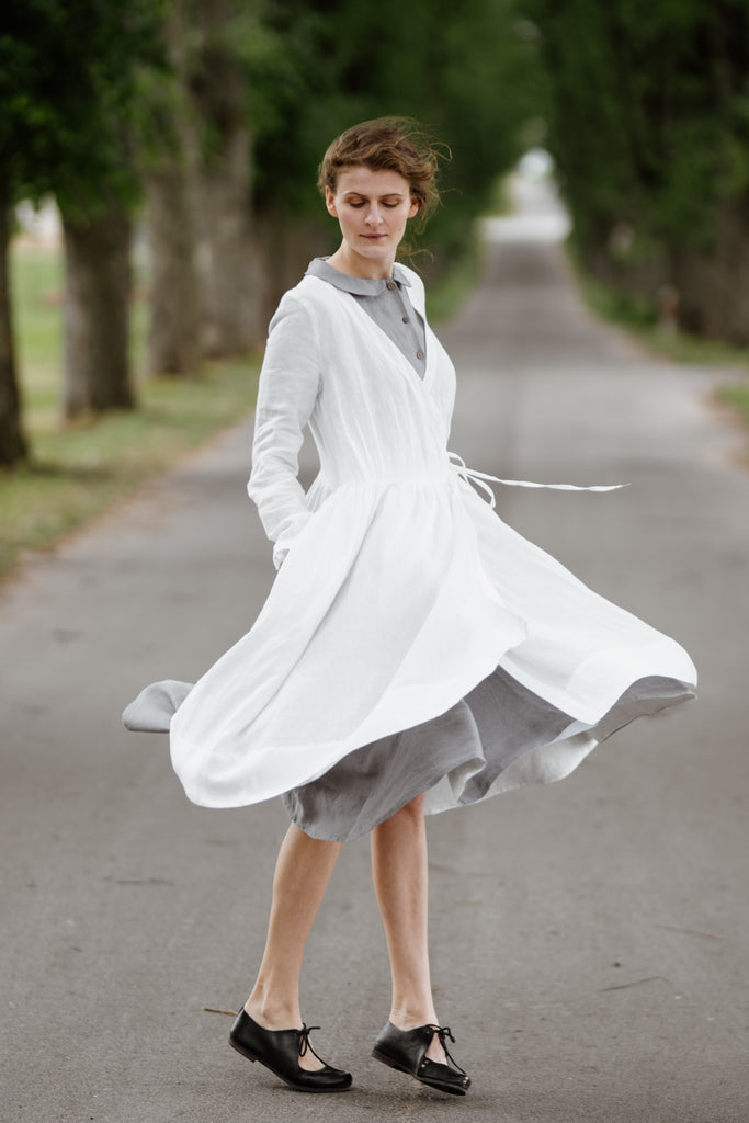 Woman wearing white wrap dress with long sleeves, picture from the front
