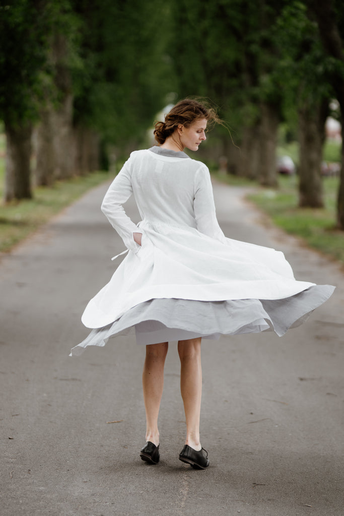 Model wearing white wrap dress with long sleeves, image from the back