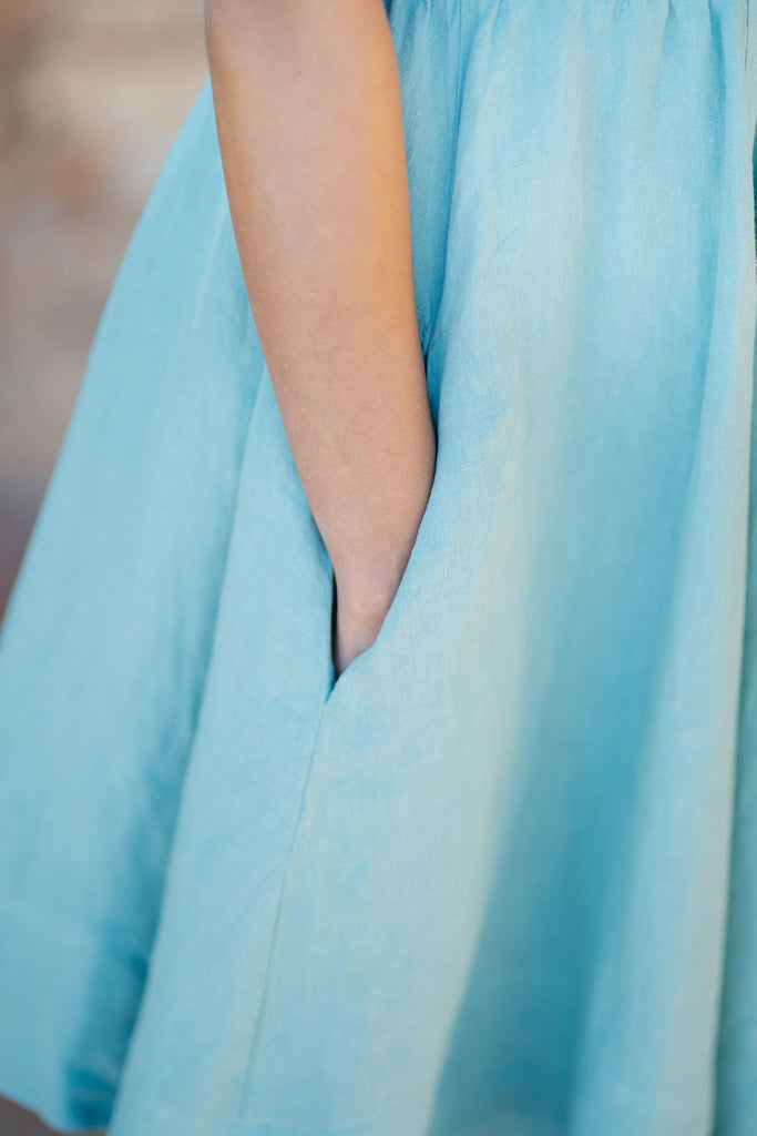 Pocket detail on a light green linen dress