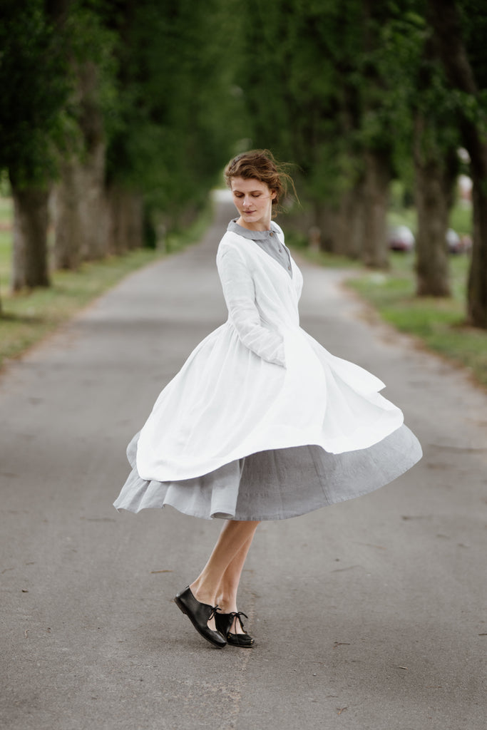 Woman wearing white wrap dress with long sleeves, image from the side