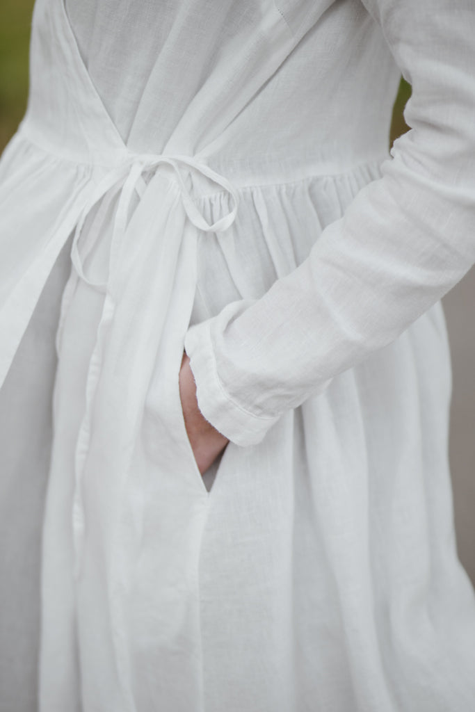Woman wearing white wrap dress with long sleeves, up close image from the side