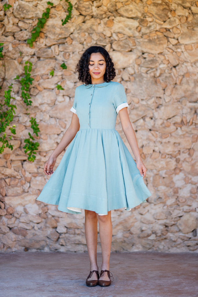 Woman in mint tea linen dress with white rolled up sleeves