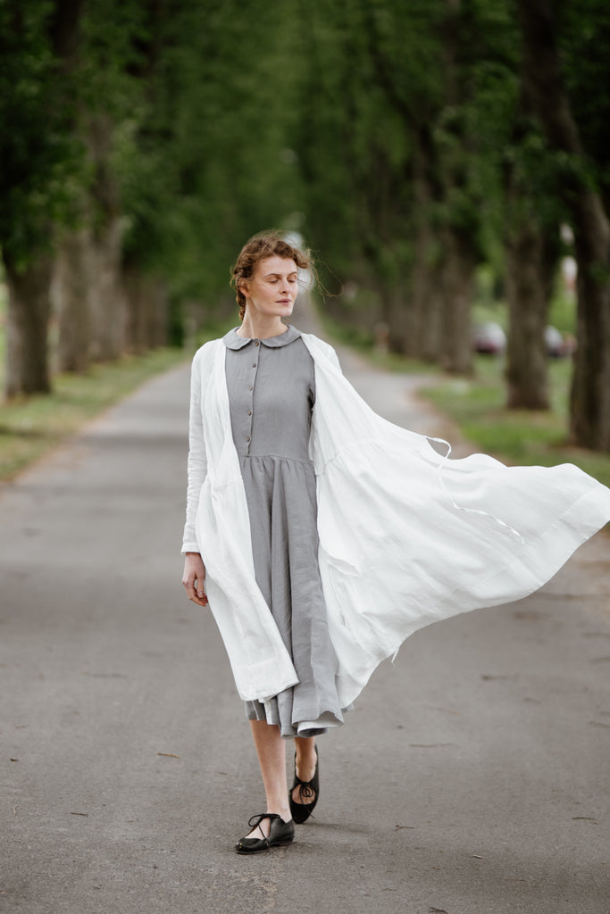 Woman wearing white wrap dress with long sleeves, image from the front