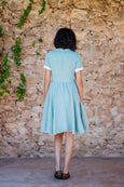 Picture from the back: woman walking towards a wall in light green linen dress