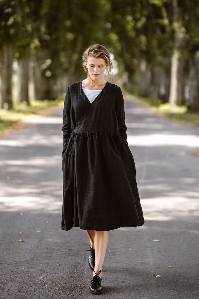 Woman wearing black wrap dress with long sleeves, picture from the front