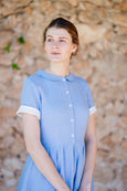 up close portrait of a model wearing baby blue linen dress with short sleeves and white buttons.