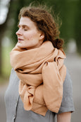 Woman wearing beige color shawl, image from the side.