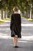 Woman wearing black wrap dress with long sleeves, picture from the back