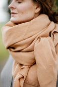 Up-close image of a woman wearing beige color shawl.