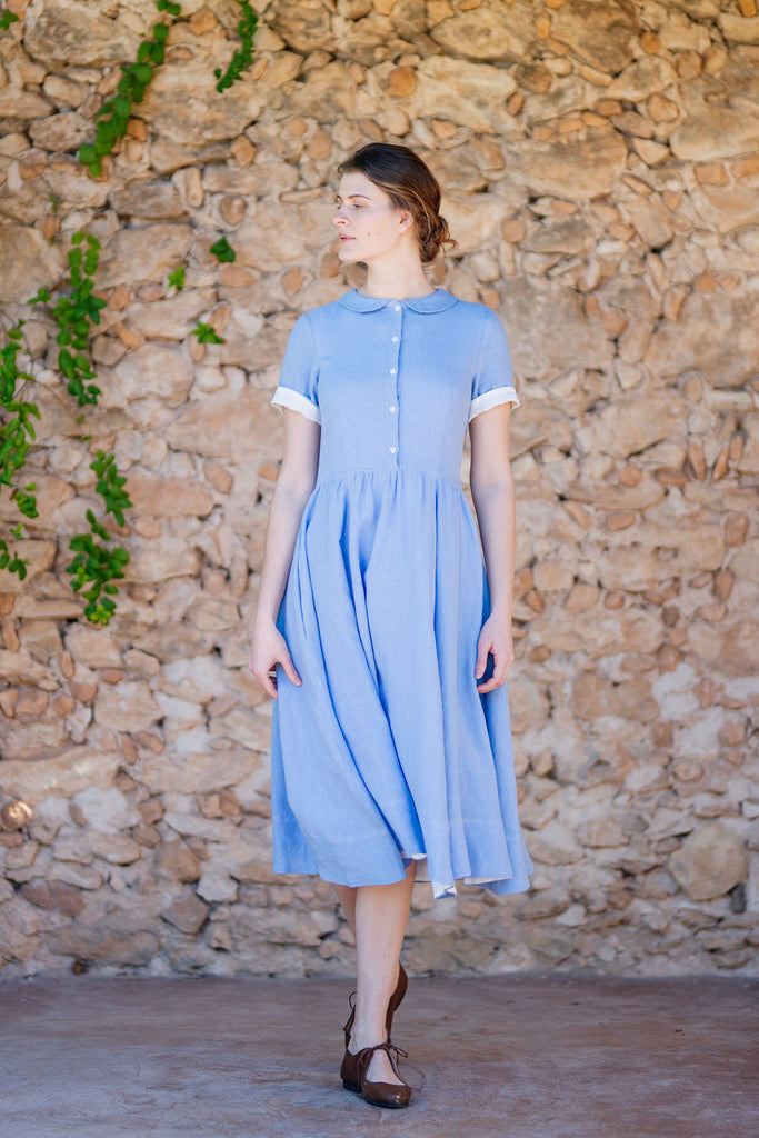 front picture of woman wearing light blue linen dress with short sleeves