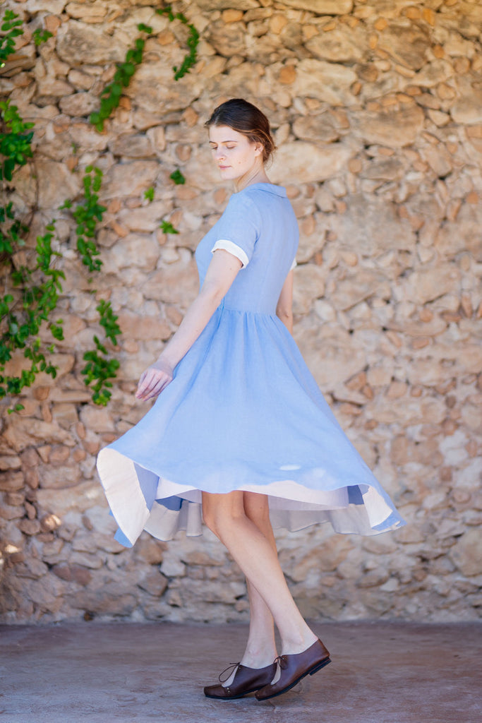 woman in a light blue linen dress with a midi full A-line skirt