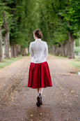 Woman pictured from the back in the linen shirt and red linen midi skirt