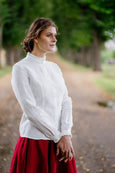 Woman in a white ruffle collar shirt with long sleeves