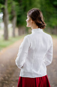 Woman's image from the back, in a white organic linen shirt