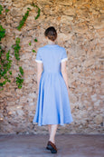 picture from the back: woman wearing a light blue linen dress