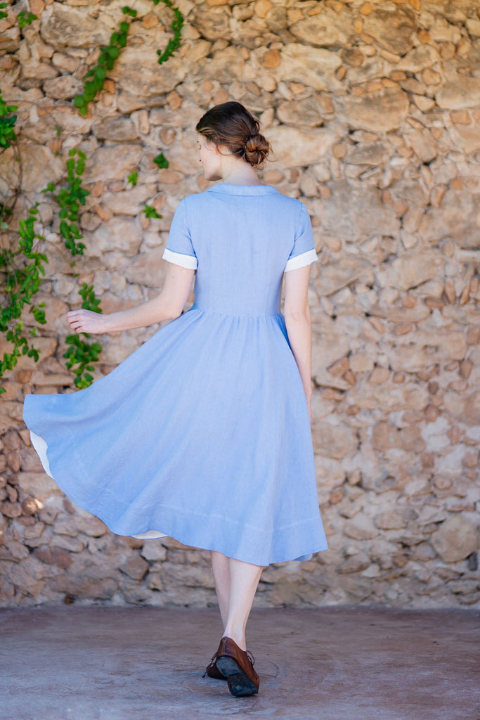 woman walking with midi linen dress in light blue color