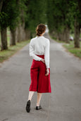 Woman wearing red color linen trousers, image from the back