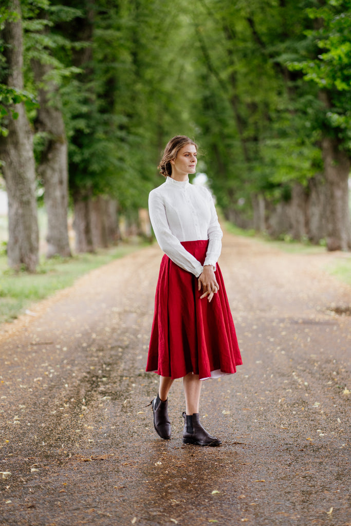 Woman in a white linen shirt paired with red linen midi skirt