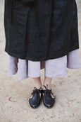 Woman wearing black linen apron, up close image from the front